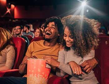 A couple laughing and enjoying a movie together