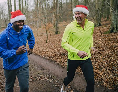 People running in a race with Santa hats on