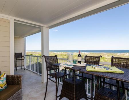Oceanfront deck with wine looking over beach