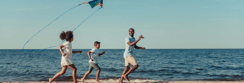 Family Running on Beach with Kite