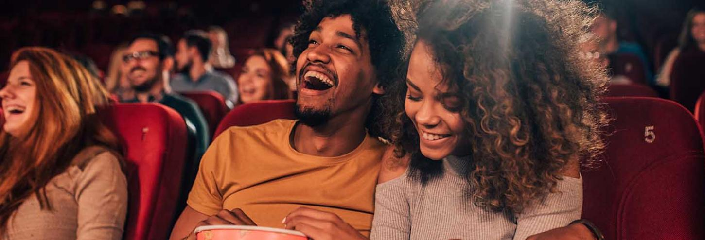 Boyfriend and girlfriend laughing and enjoying a movie together