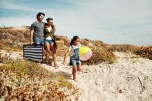 family beach vacation, little girl carrying beach ball, father carrying picnic basket to beach