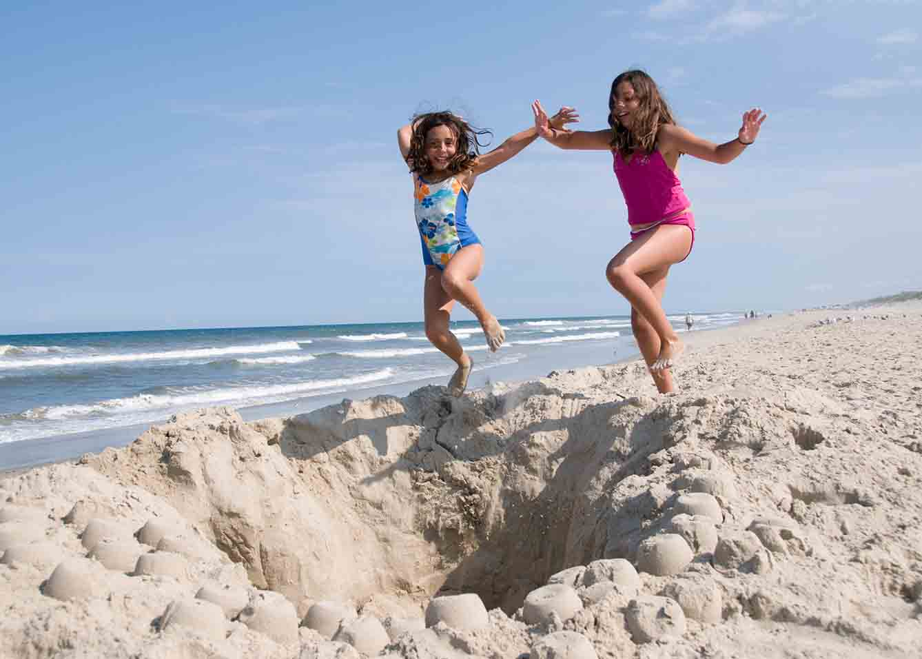 Two girls playing in the sand at Kure Beach
