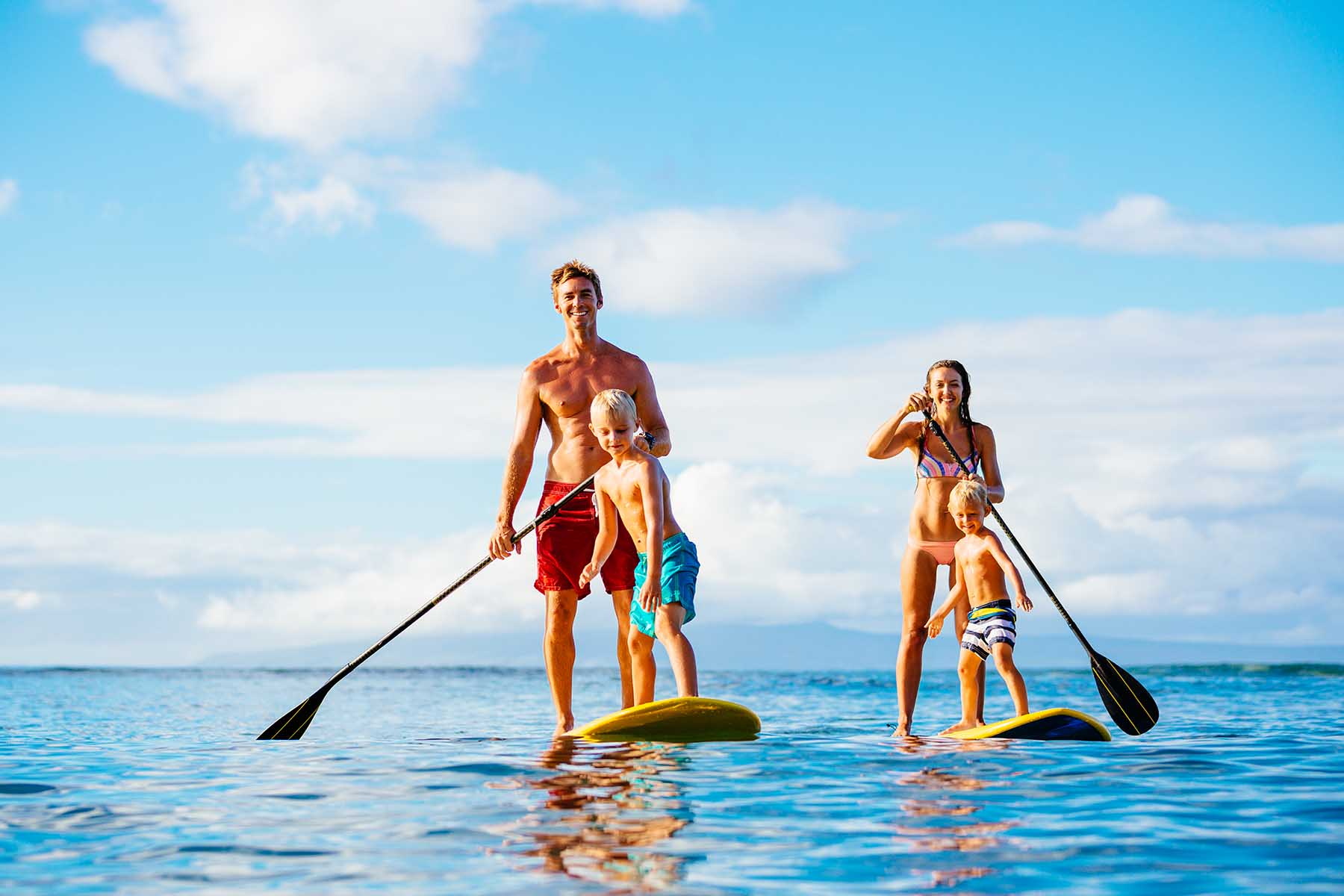 Parents with their kids enjoying stand up paddleboards