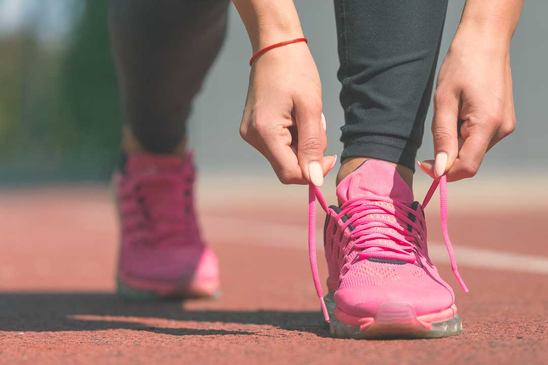 Girl tying her pink racing shoes